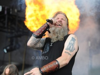 Lead singer of Amon Amarth singing on stage with a fireball behind him