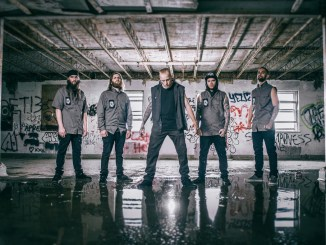 Obliterate band members standing in what looks like a parking garage or factory