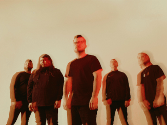 Of Virtue band members, all wearing dark colors in a white room, blurry (possibly meant for 3D glasses)
