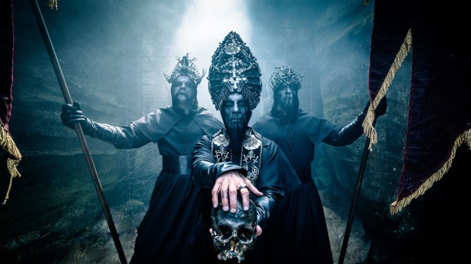 Behemoth picture with a Satanic priest, holding a skull, with 2 guards armed with spears