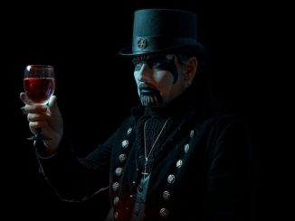 King Diamond in the dark, holding a glass of red wine