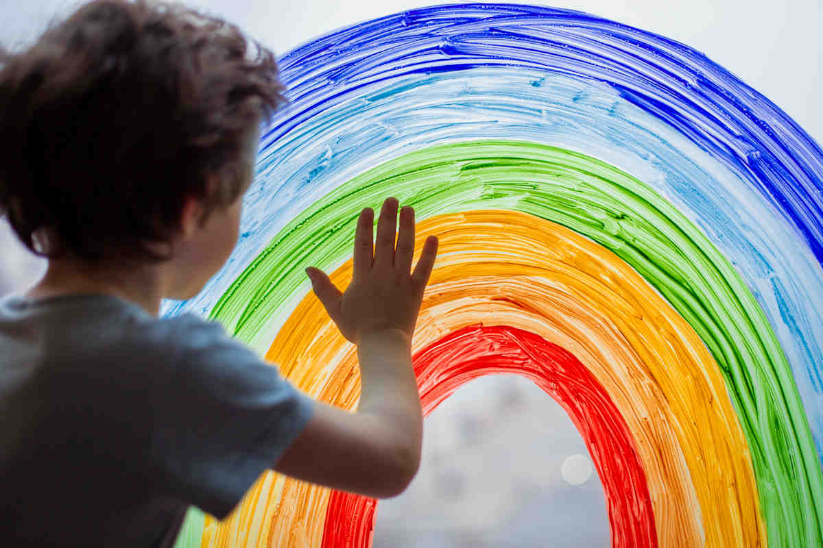 Child with hand touching a window painting