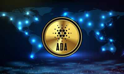 Picture of a Cardano (ADA) coin in front of a map of the world