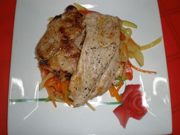Filetes de cerdo acostados en verdura al dente con papas y ajos