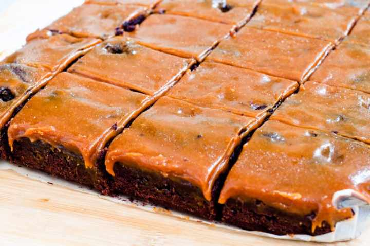 Brownie on baking paper, sliced in square portions.