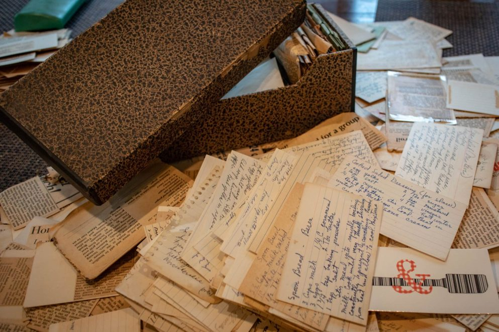 a cardboard recipe box and a pile of recipes on index cards