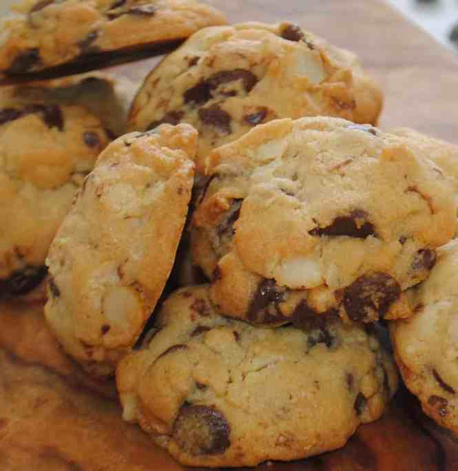 Chocolate chip cookies with macadamia nuts piled up on timber board