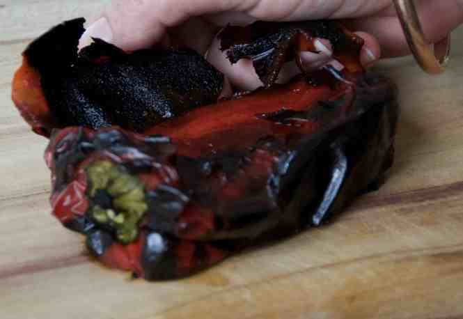Chargrilled bell peppers on chopping board having 'blackened' skin removed after sweating