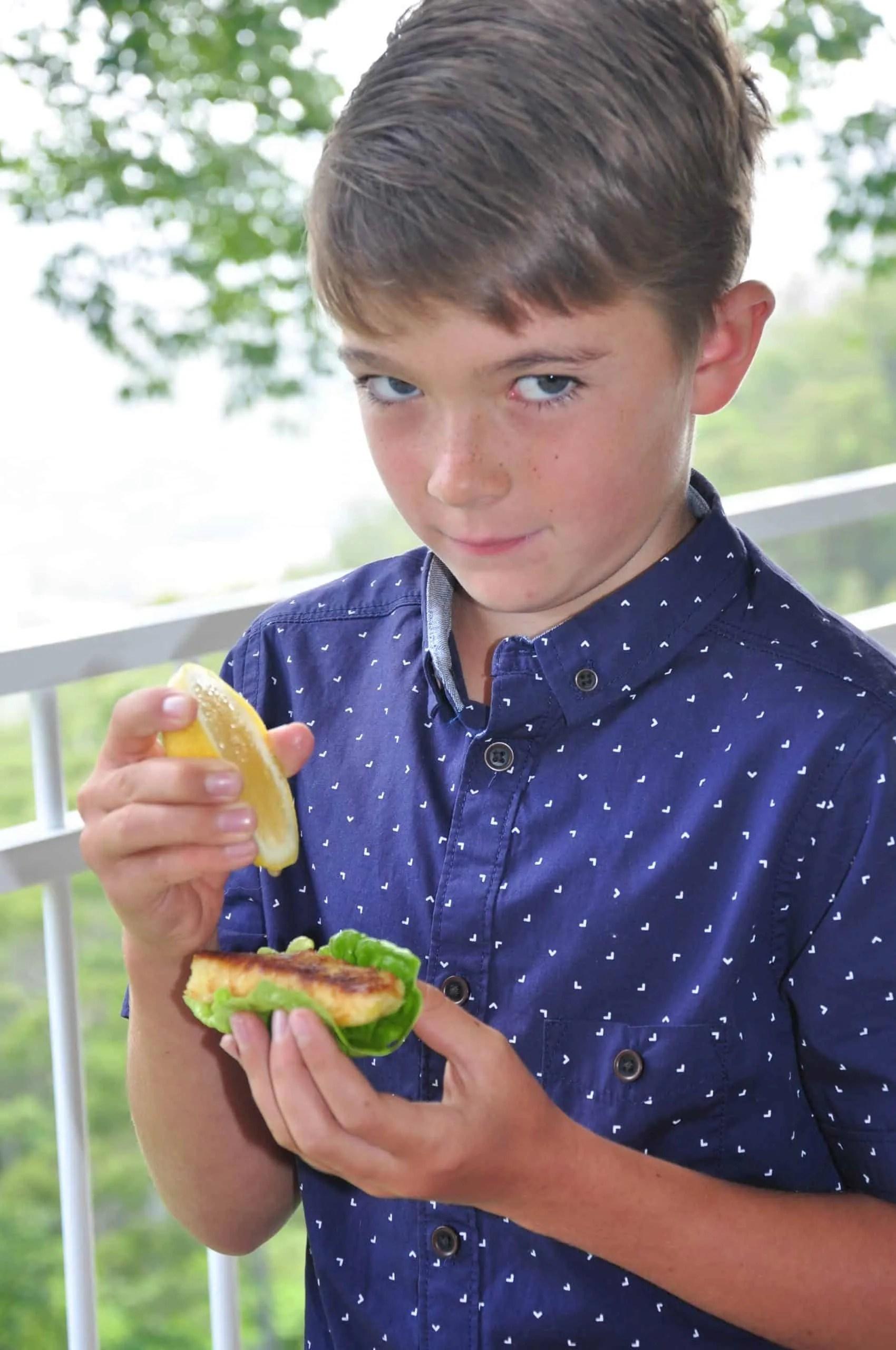 Ollie on verandah holding cos lettuce leaf with haloumi fries