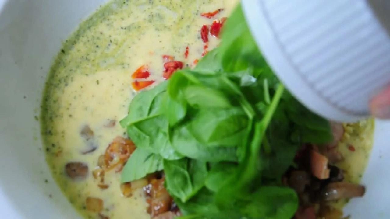 Best breakfast strata - casserole mixture in white bowl with spinach added