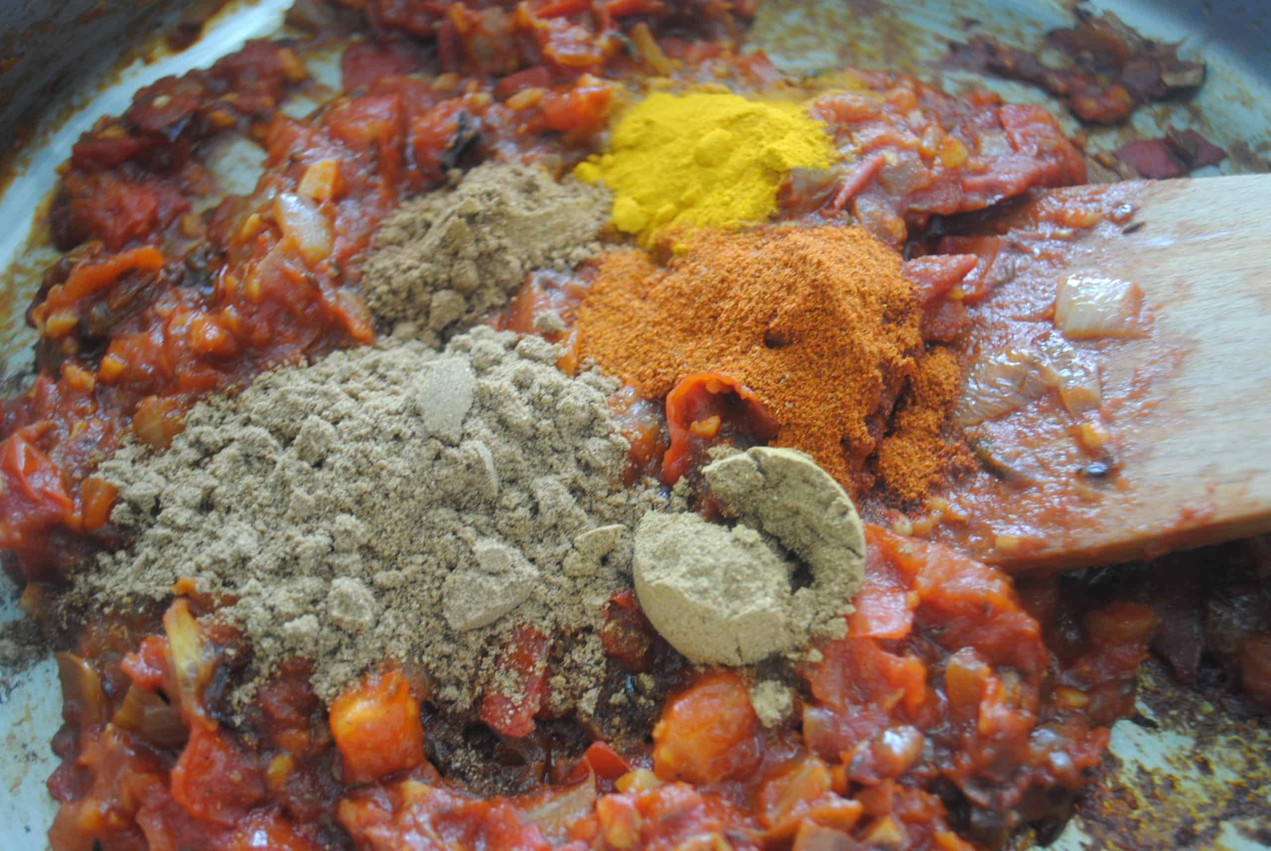 indian vegetable curry adding spices to wok