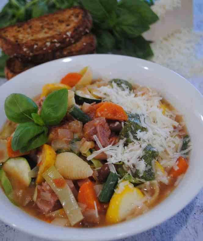 minestrone soup ready to serve in a white bowl with grated parmesan and pesto sauce