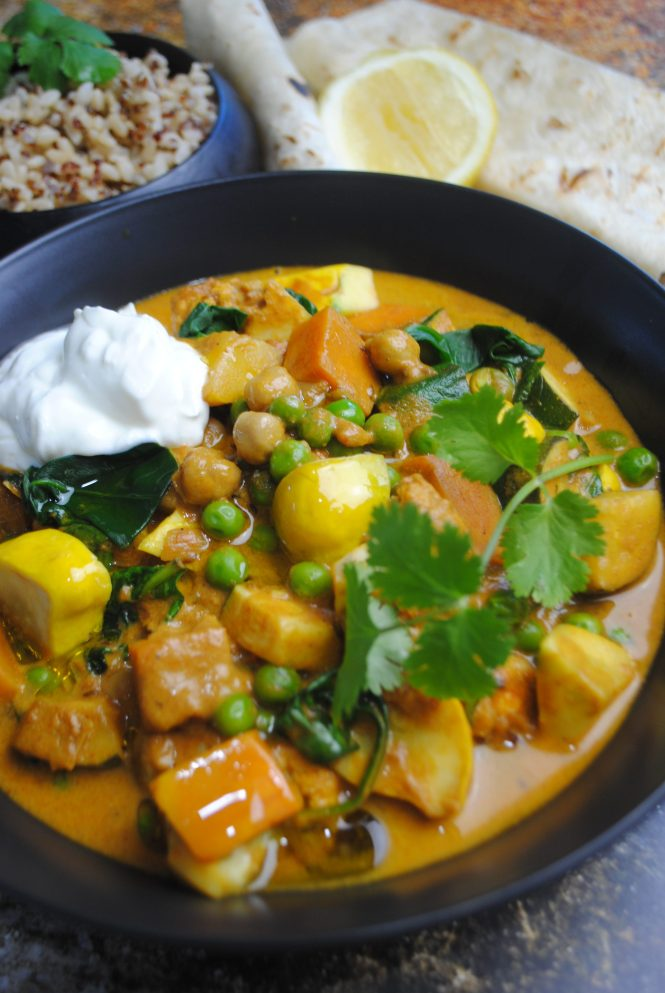 Indian vegetable curry ready to eat with vegetables and background of rice, lemon and flatbreads