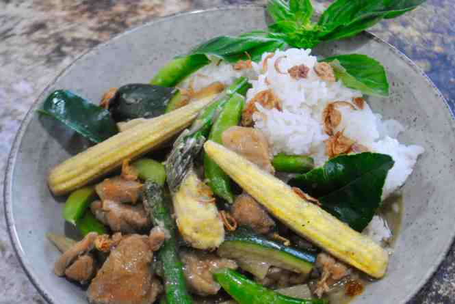 Thai green chicken curry served with rice and garnished with basil