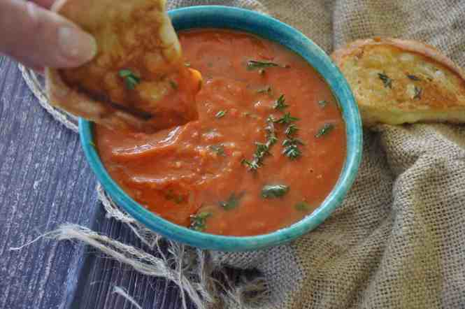 Roasted tomato and garlic soup in a blue bowl with a cheese toastie