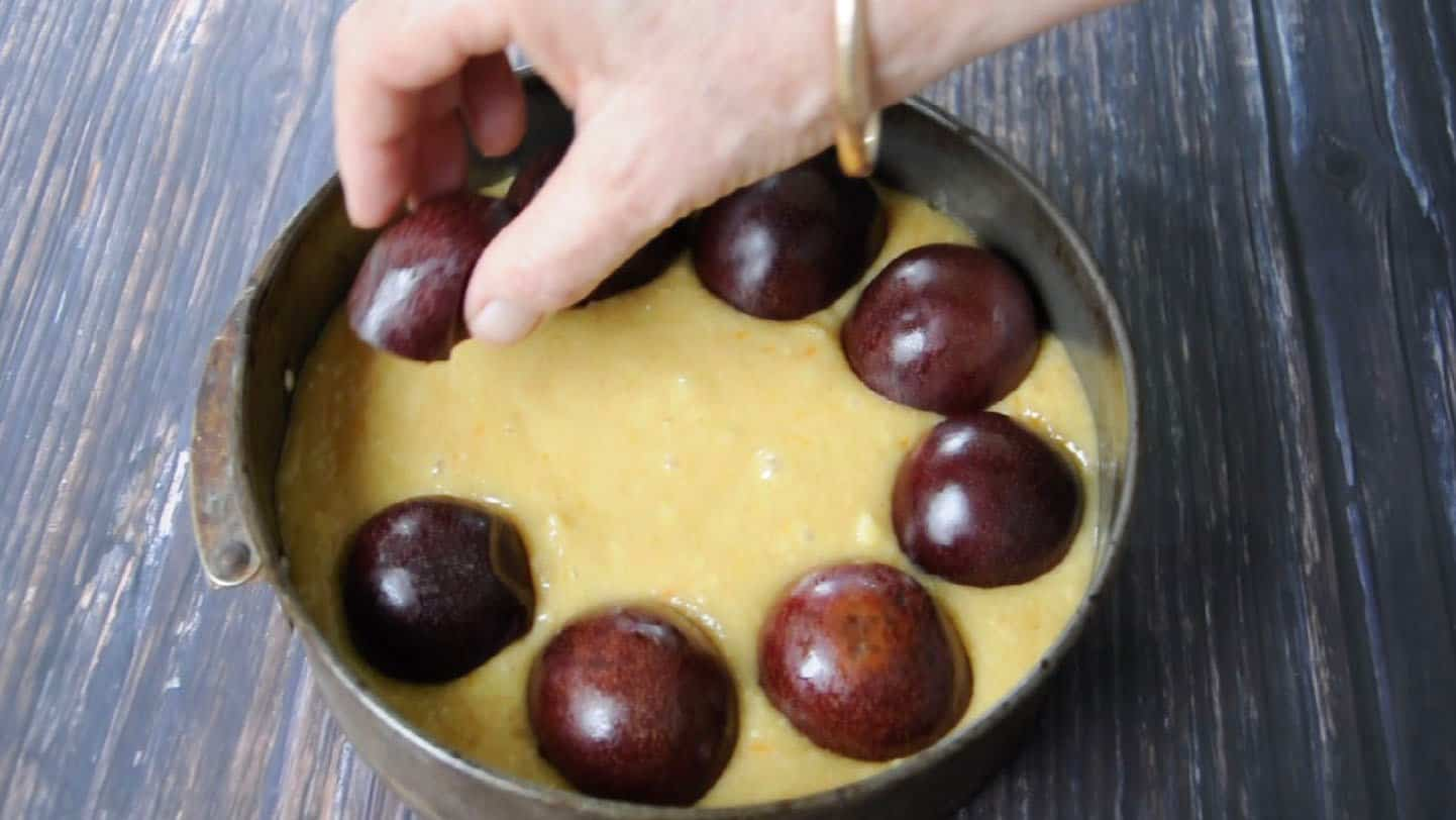 plum streusel cake placing plum halves onto cake batter with a hand with a gold bangle