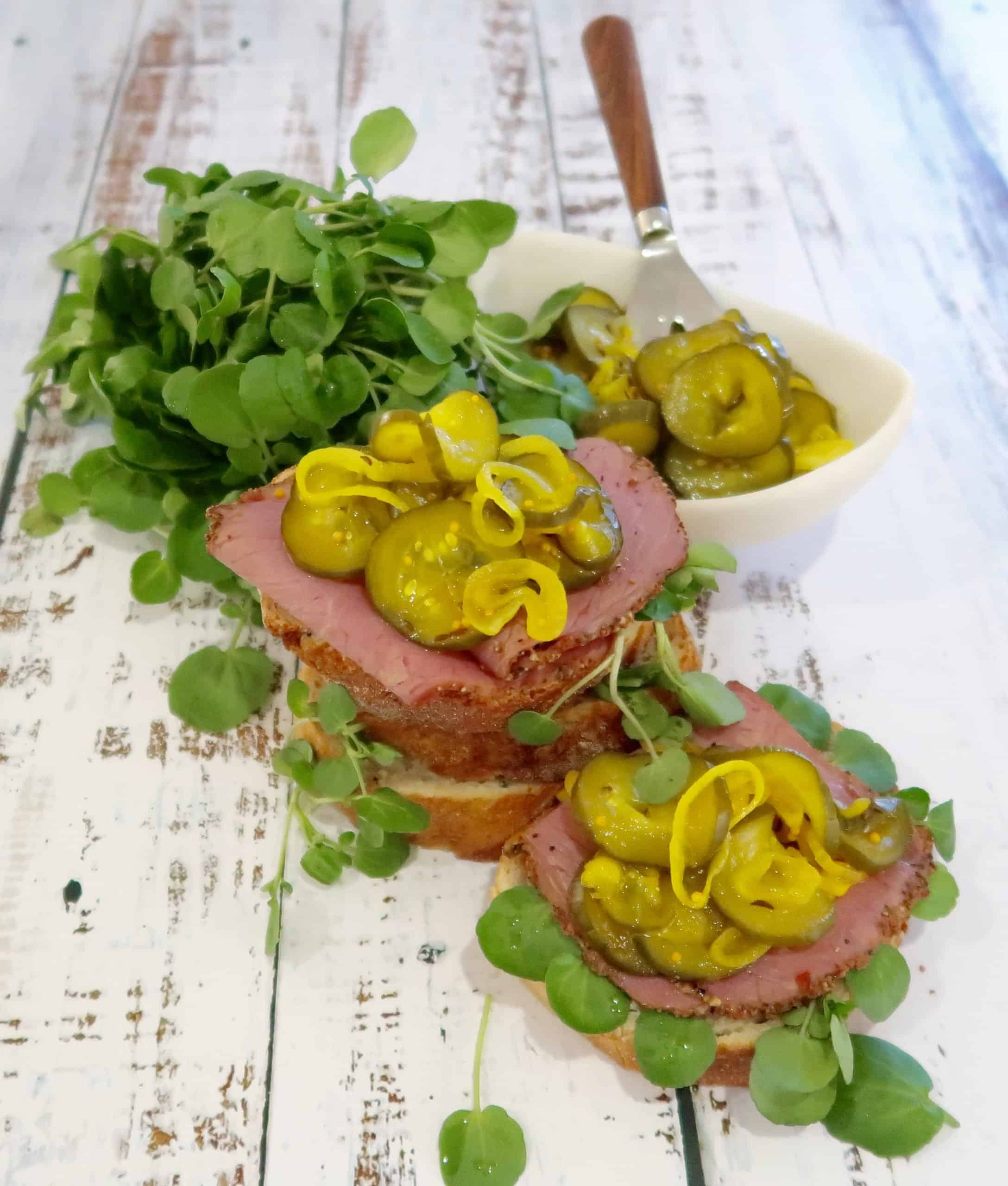 easy bread and butter cucumber pickle served on pastrami and bread with watercress