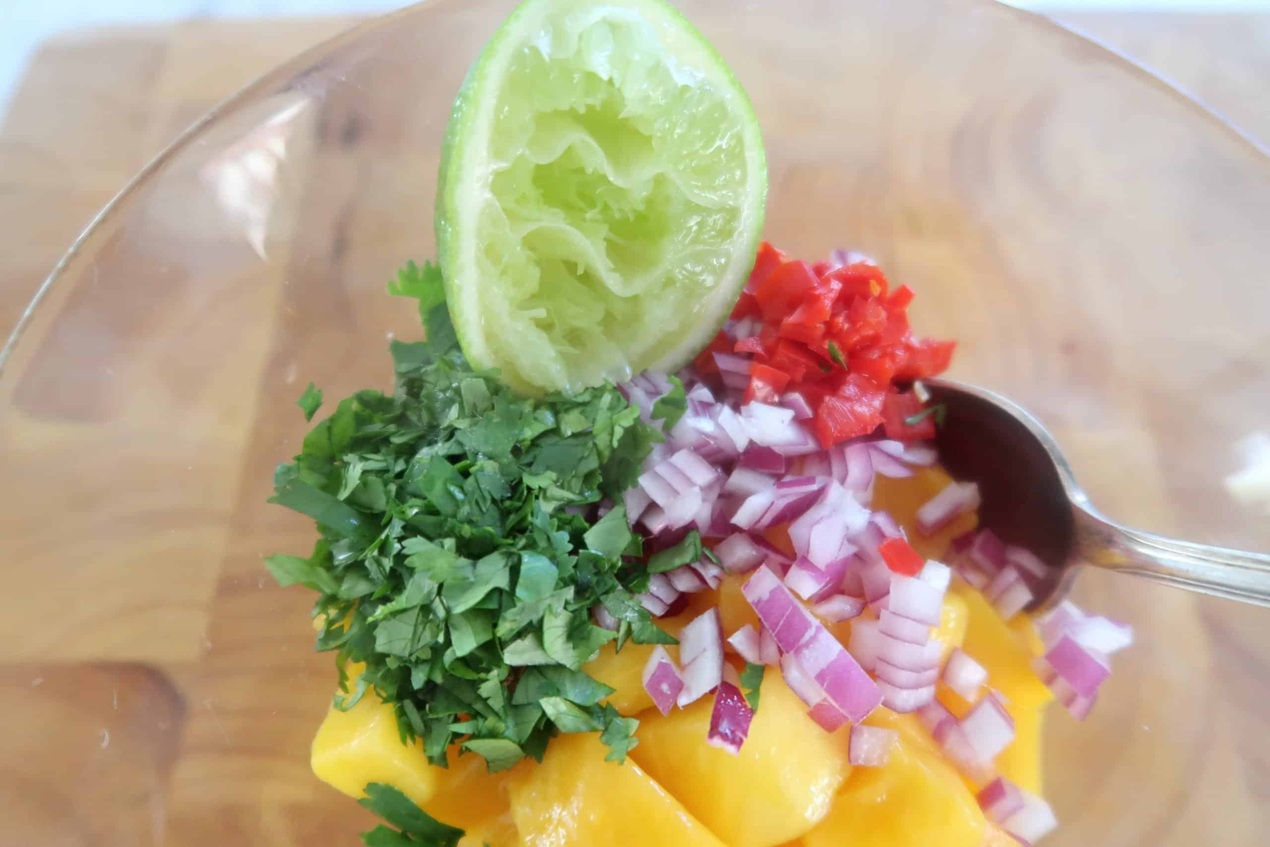 Mexican prawn, mango and avocado salad ingredients in a glass bowl ready to mix
