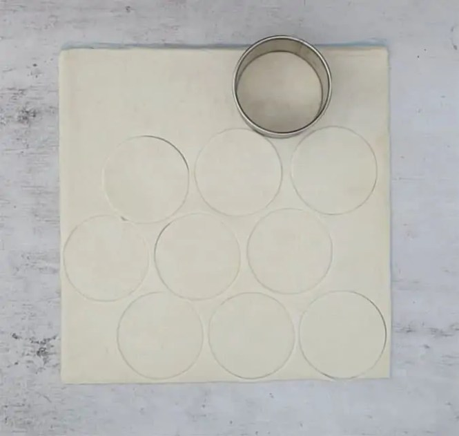 sheet of puff pastry with cut out pieces ready to make Easy Cheese Puff Tarts