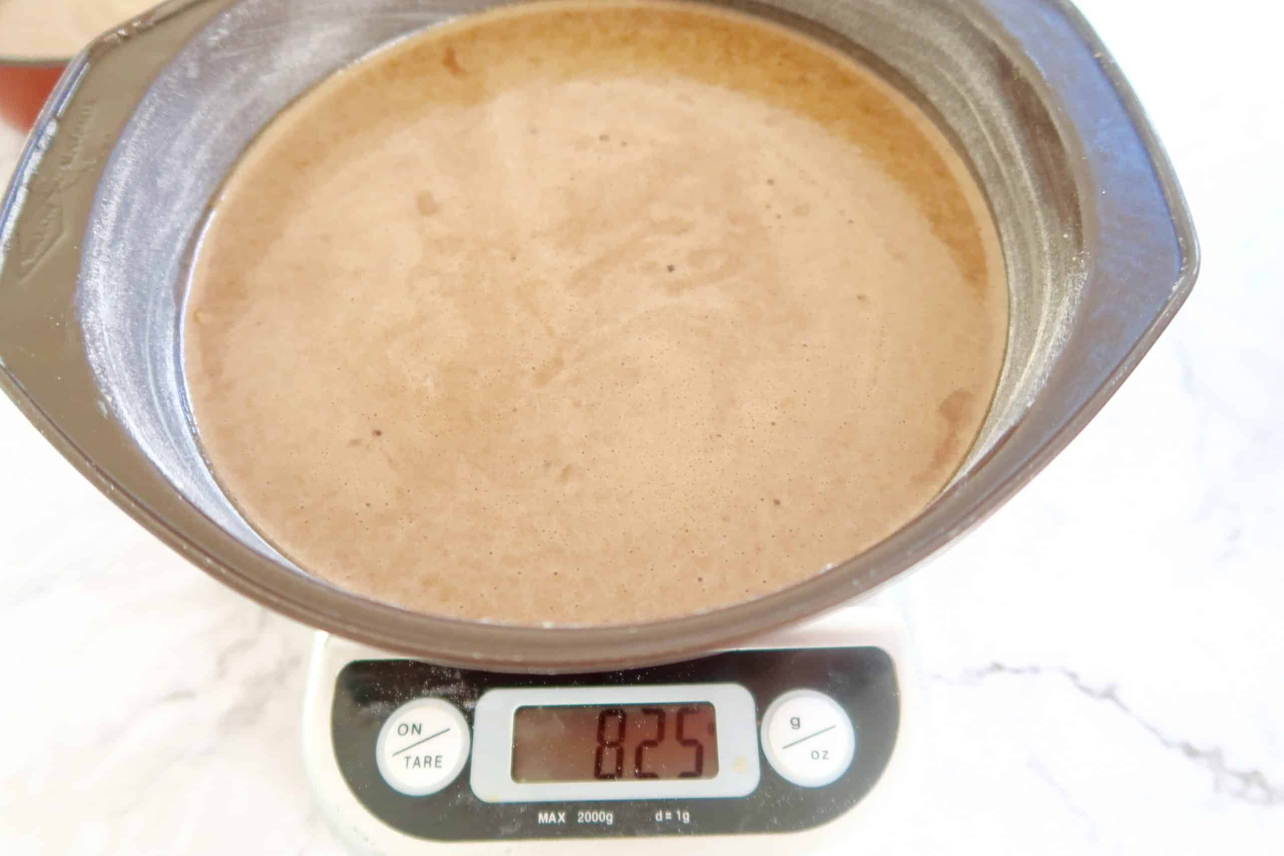 easy moist chocolate cake with buttercream icing batter in cake tin and sitting on a scale to measure the weight of the batter