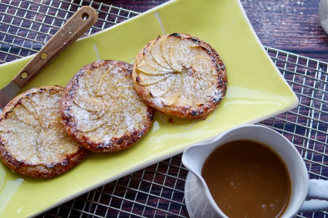Three apple tarts on a green plate with easy salted caramel sauce in a white jug