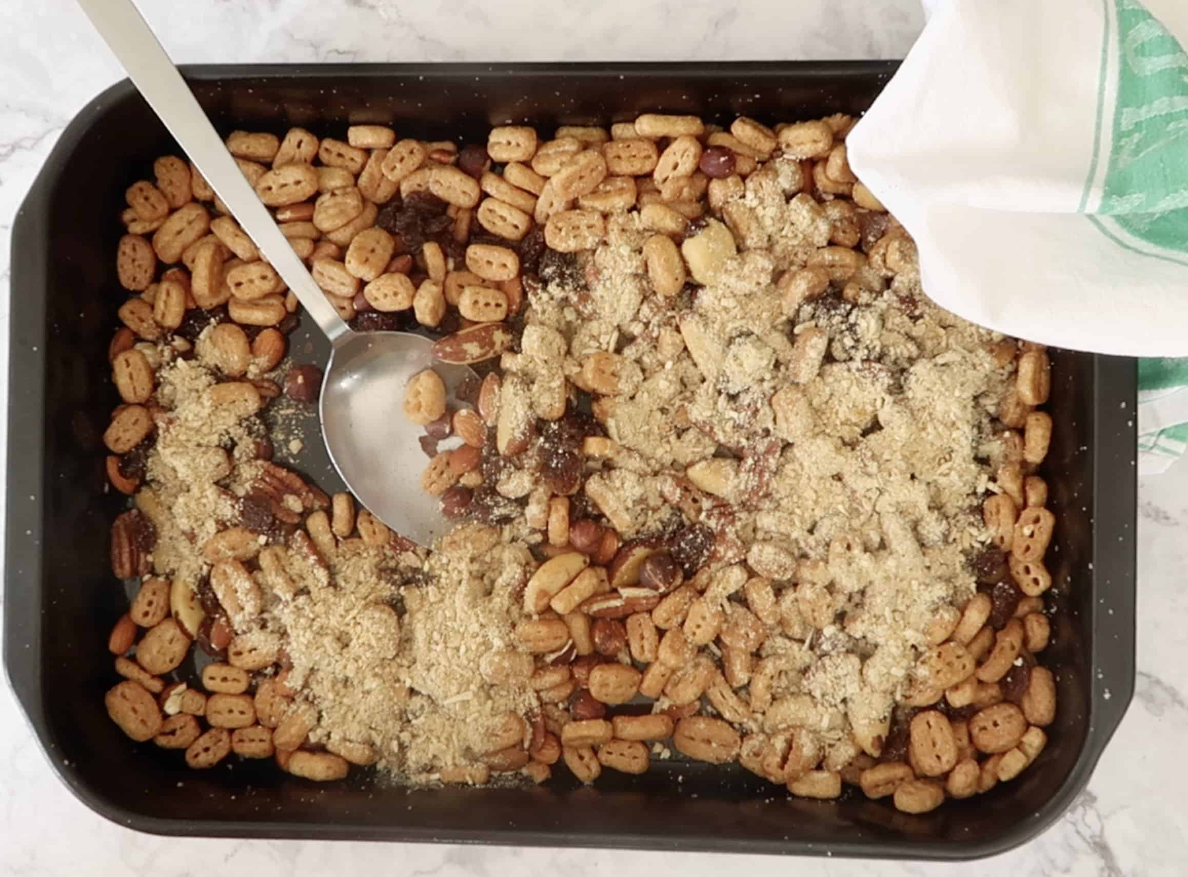 dish of roasted Nutrigrain with a metal spoon and mixed nuts, raisins and the seasoning mix added to make nuts and bolts