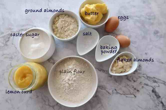 lemon curd and almond butter cake ingredients laid out in white dishes with the ingredients labelled on a marble bench