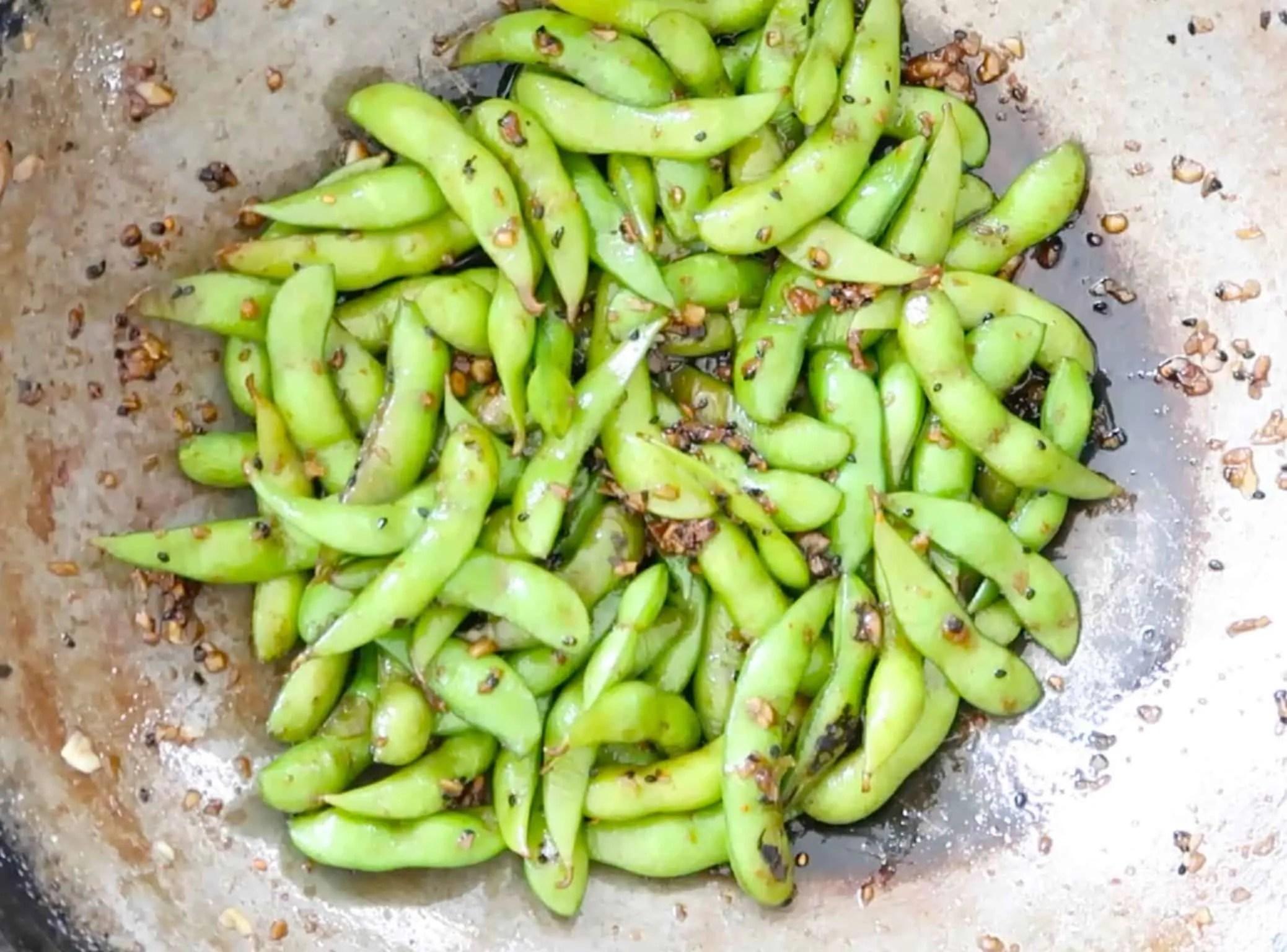 garlic chilli edamame in a wok ready to serve