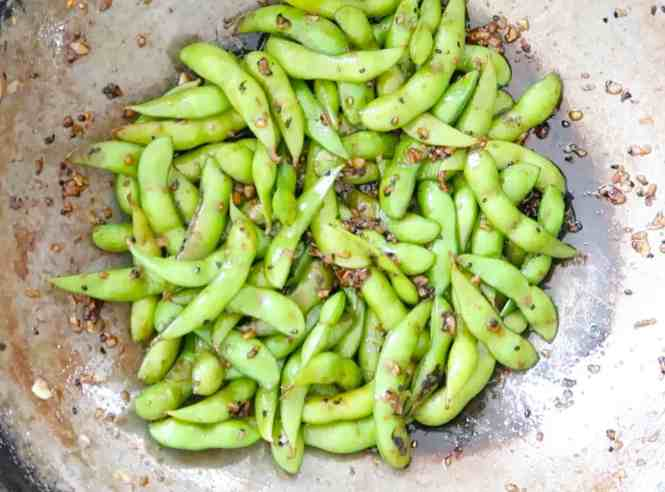 garlic chilli edamame in a wok ready to serve