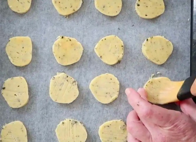 slices of Parmesan and Rosemary Shortbread on a baking tray being glazed with egg