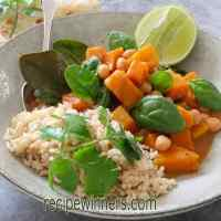 Thai Pumpkin, Chickpea and Spinach Curry in a blue bowl with a lime wedge