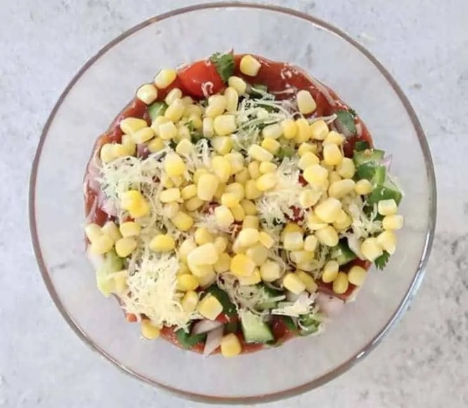 a layer of corn is added to a glass bowl while making Mexican Layered Dip