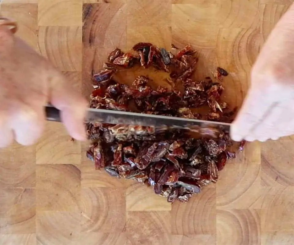chopping dates on a board to make Sticky Date Roll