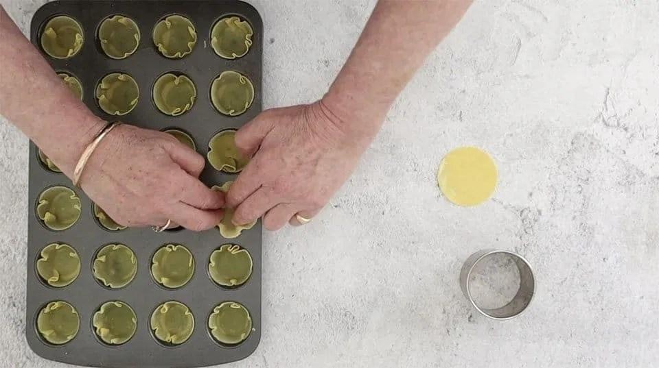placing cut wonton wrappers into a mini muffin tin to make Cajun crab tarts
