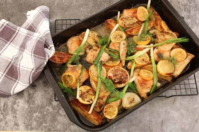 black airing rack with chicken fennel lemon tray bake resting on it