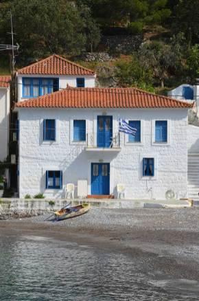 Maison blanche aux volets bleus en bord de mer à Kyparissi