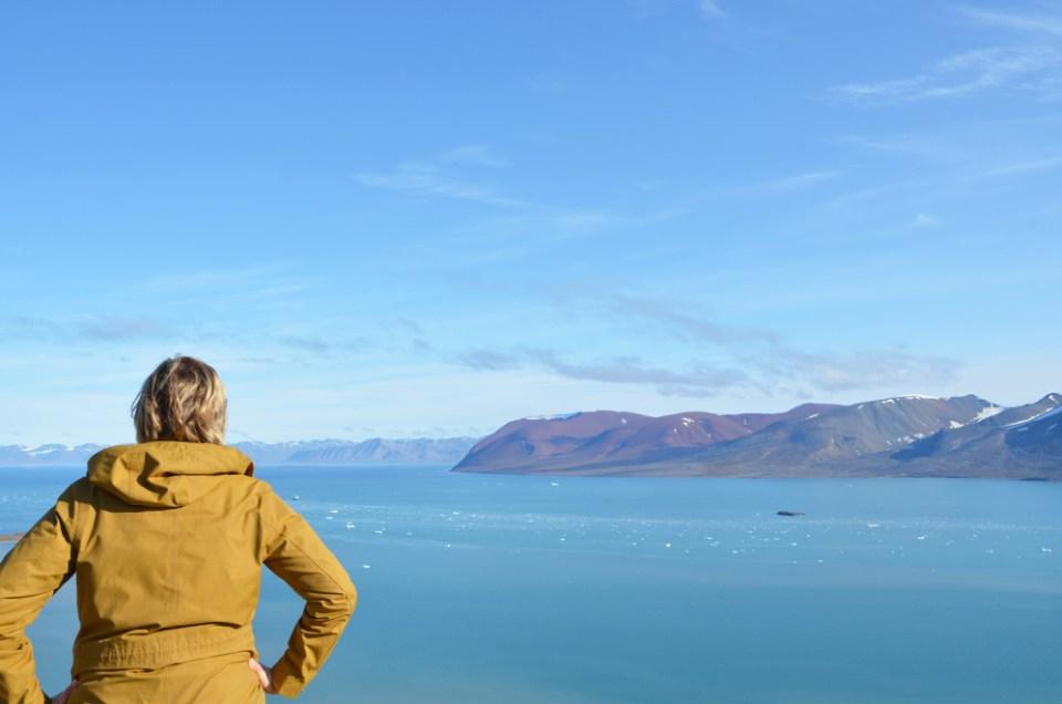 Charlotte de dos devant le paysage de la Baie de Monacobreen, Svalbard