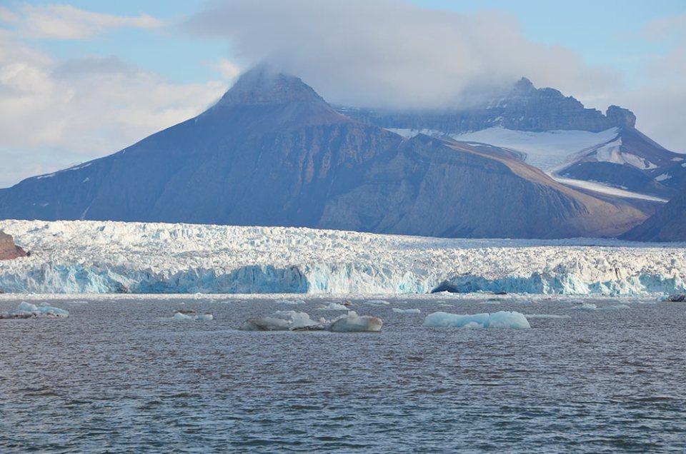Montagne noire au-dessus d'un énorme glacier du Svalbard