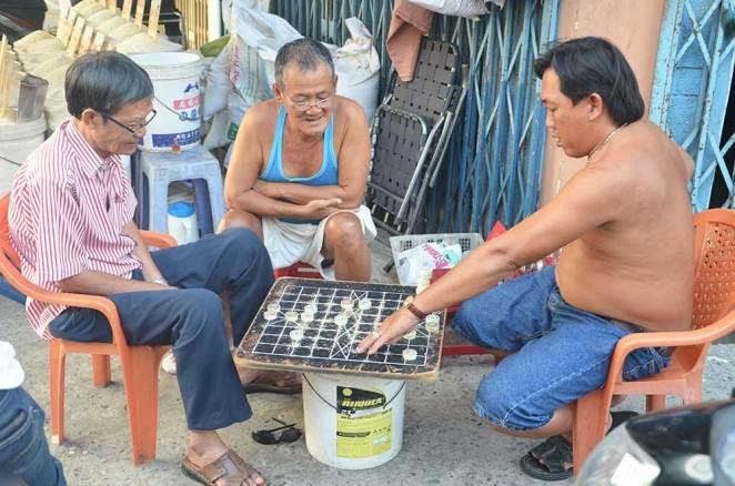 Des Vietnamiens qui jouent à un jeu de société dans la rue, Can Tho, Vietnam