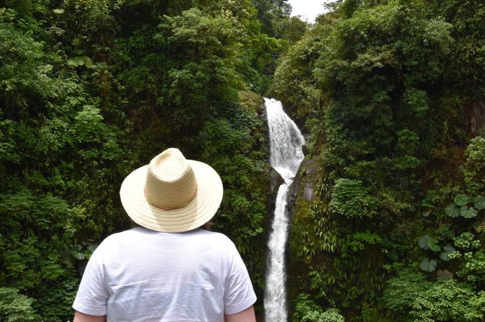 Marie-Catherine face à une cascade au bord de la route au Costa Rica
