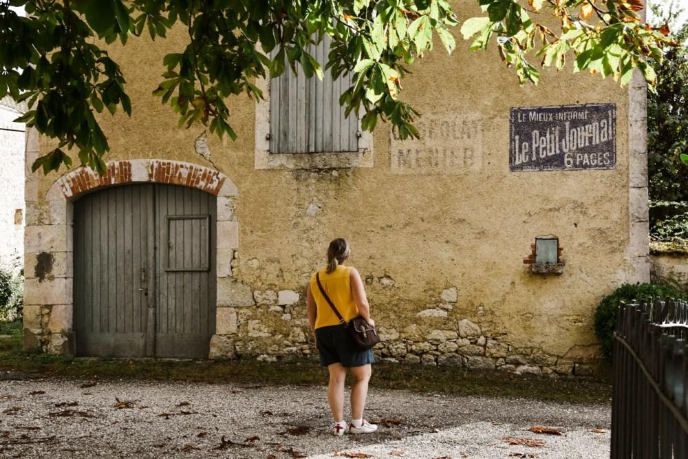 Marie-Catherine devant la façade d'une maison du village de Tournecoupe, Gers
