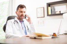 Pictured is a healthcare professional at a desk on the phone. In depth telephone interviews can be conducted at your convenience at a pre-scheduled time.
