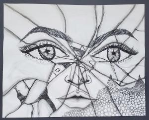 Broken mirror showing a shattered image of a woman's face