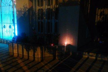 Kleine Kerzen im Innenhof auf einer Mauer.