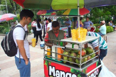 Angel hält meinen erstandenen Becher der mango espaghetti, während der vendedor das Wechselgeld zusammensucht.