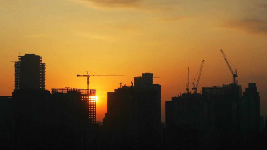 The sun sets behind an ongoing infrastructure project in Asia