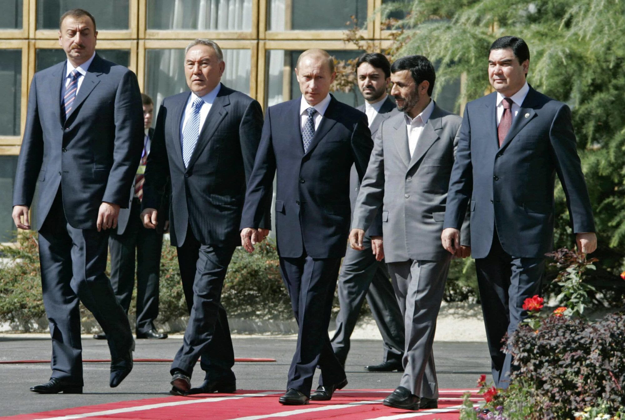 Government officials from various nations walk in a line; corridor.