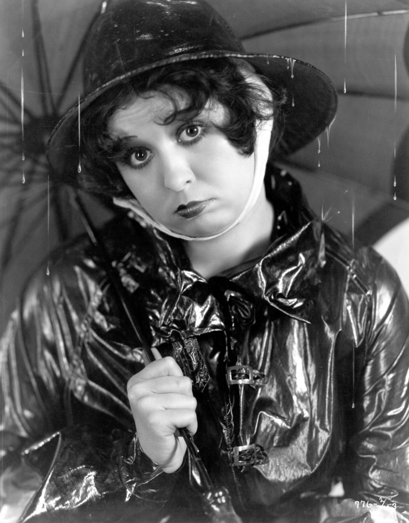 circa 1934: Helen Kane (1904-1966), formerly Helen Schroeder, the original 'boop-boopa-doop' singer and actress signed by Paramount, sheltering beneath an umbrella. (Photo by Otto Dyar/Hulton Archive/Getty Images)