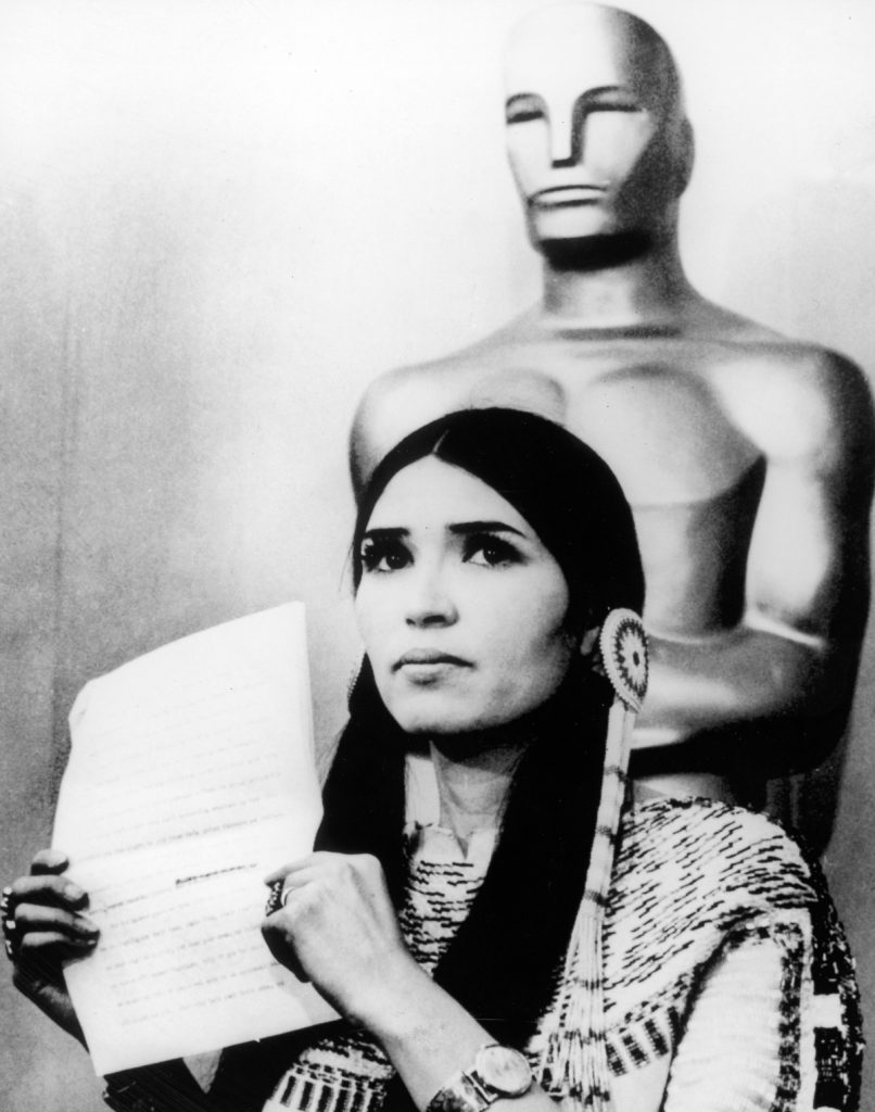 27th March 1973: Sacheen Littlefeather (Native American actress Maria Cruz) holds a written statement from actor Marlon Brando refusing his Best Actor Oscar on stage at the Academy Awards, Los Angeles, California. (Photo by Hulton Archive/Getty Images)