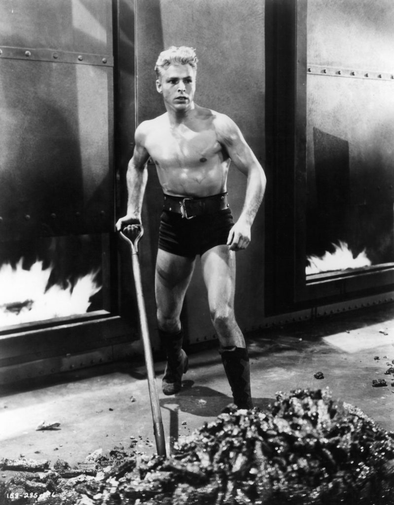 Buster Crabbe shoveling in a scene from the film 'Flash Gordon', 1936. (Photo by Universal/Getty Images)